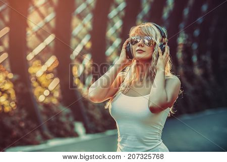 Young teenage style woman with sunglasses and headphones walking on urban street