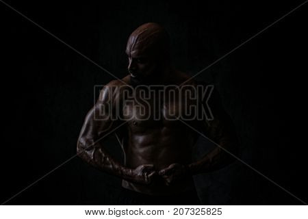 Strong man bodybuilder. Very dark dramatic colors. Tattoo on hand.