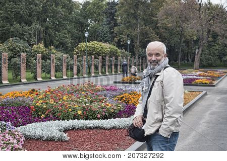 A man of mature years at a flower bed in Shevchenko Park in Kharkiv