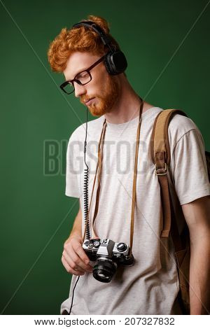 Yong readhead bearded hipster with backpack holding retro camera, listening to music, over green background