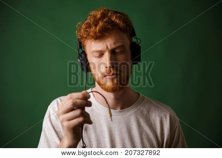 Close-up of young curly readhead hipster holding cord of headphones, with closed  eyes, over green background