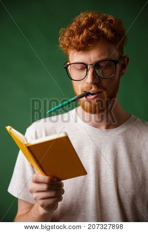 Smart readhead student in glasses with pen in his mouth, holding notebook, over green background
