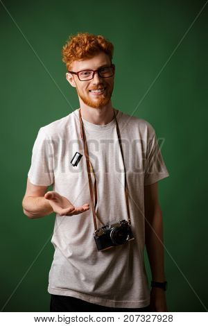 Handsome stylish readhead hipster in white tshirt with retro photo camera, looking at camera over green background