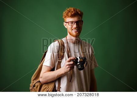 Shot of readhead bearded hipster with retro camera and backpack, standing over green background