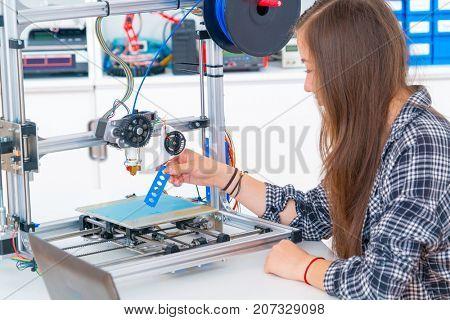Schoolgirl prints 3d model from plastic on 3d printer