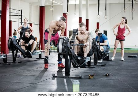 Clients Looking At Friends Using Rowing Machines