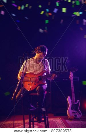 Flying colours against full length of guitarist performing at concert