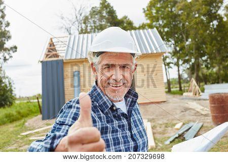 Senior as master craftsman holding thumbs up
