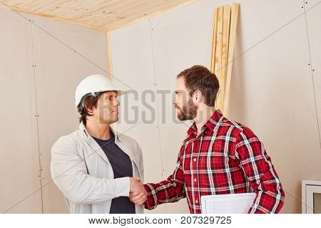 Two craftsmen shaking hands and closing agreement