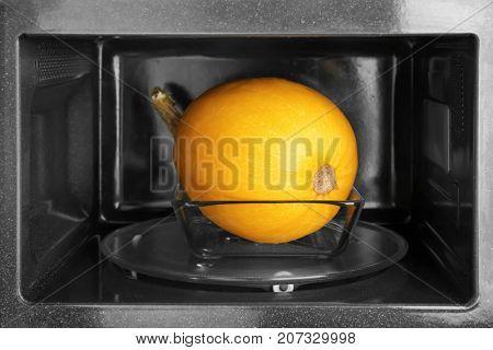 Glass dish with ripe spaghetti squash in microwave