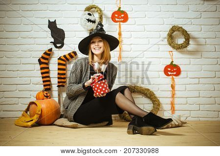 Halloween woman smiling with gift box and bag. Surprise and present concept. Girl in witch hat sitting on floor. Happy holiday celebration. Pumpkins stockings wreaths cat mummy decorations on wall