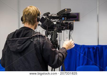 Operator preparing tv camera to the live broadcast