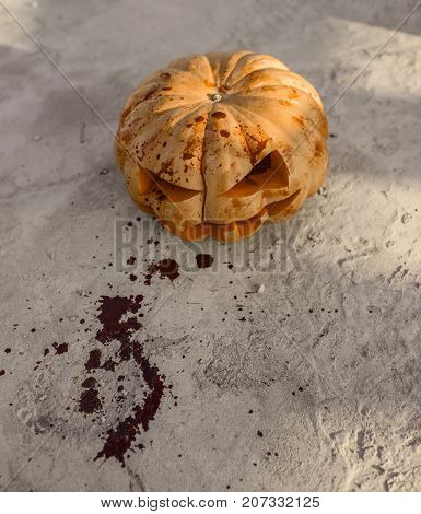 Halloween pumpkin bleeding on cement background. Jack o lantern with red blood and bloodstains on ground. Squash with carved smiley face. Autumn tradition and symbol. Holiday celebration concept