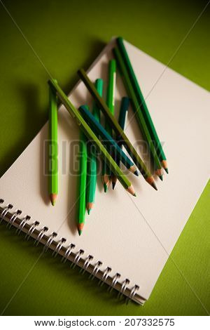 green shades pensils on green paper pad