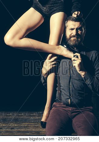 Love and relations dominating. Man in shirt isolated on black background matriarchy. Legs of woman in shoes at man with beard. Guy at table with female legs. Romance and couple in love.