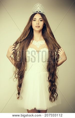 Girl has fashionable makeup and healthy hair on grey background. Haircare and prom queen. Beauty salon and wedding fashion. Hairdresser and cosmetics. Woman with long hair white dress and crown.