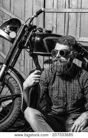Bearded man hipster biker brutal male with beard and moustache in vintage sunglasses sits with bottle near motorcycle on wooden background
