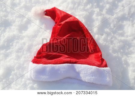 Santa red hat on snow. Santa claus cap on snowy background. Christmas and new year. Winter white landscape. xmas holidays celebration concept.
