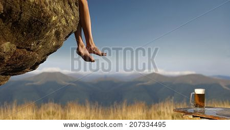 Beer in glass mug on wooden table and barefoot female legs hanging on stone on mountain landscape on blue sky. Bliss and refreshment concept. Travelling and wanderlust