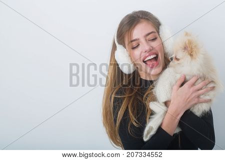 Woman with small dog of Pomeranian Spitz. Xmas party and vacation. Dog in hand of woman on white background. Girl with happy face in gloves and ears. New year of dog and winter holiday celebration.