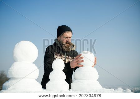 New year guy on blue sky with snow figure. Snowman family made of white snow Winter holiday vacation and xmas party celebration. Christmas man with long beard. Santa claus hipster in coat and snowman.