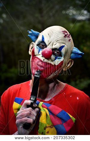 closeup of a scary evil clown in the woods wearing a dirty costume blows his gun