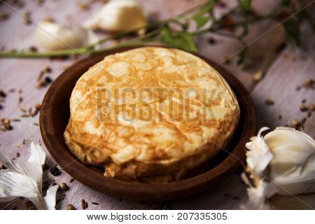 closeup of an earthenware plate with a typical tortilla de patatas, spanish omelet, on a rustic wooden table