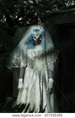 a scary evil clown wearing a dirty and ragged bride dress, at the door of a rustic shelter, in a disturbing rural landscape