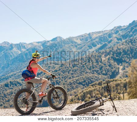 Photo of woman in helmet on bicycle showing hand