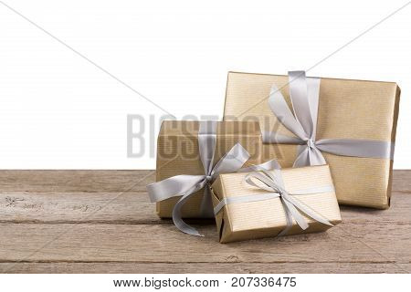 Group of gift boxes wrapped with golden paper and silver satin ribbon on wood at white background. Modern presents for any holiday, christmas, valentine or birthday