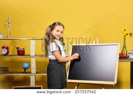 Schoolgirl With Confident Face And Ponytails Stands In Classroom