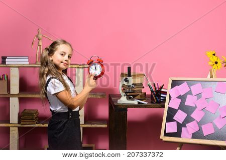 Kid And School Supplies, Pink Background. Schoolgirl With Happy Face