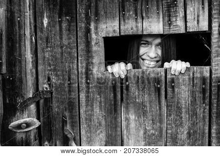 Portrait of a smiling woman peering through the crack in the barn door. Black-and-white photo.
