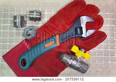 adjust wrench power grip and elements of water and gas shutoff valves on a working protective glove flat lay