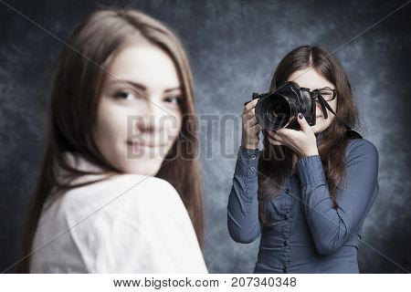 Photo Shooting At The Studio. Young Beautiful Female Model Poses For Young Woman Photographer Photog