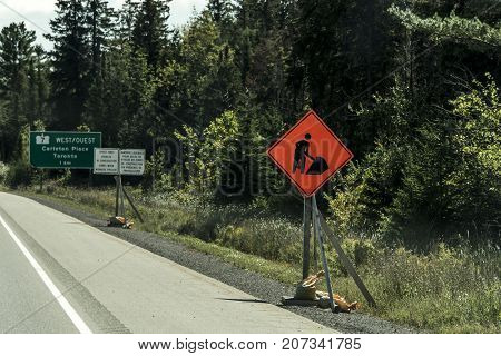 Orange construction worker sign at a road into the distance on trans canada