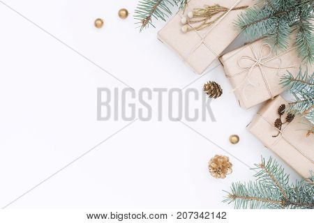 Three gift boxes Christmas decorations spruce branches and pine cones on white background. Top view holiday composition.