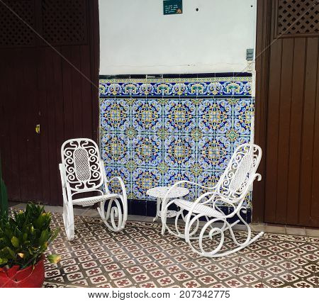 Rocking chairs in Cuba in front of mosaics on wall
