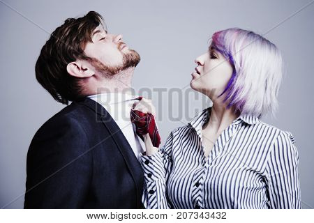 Dominant female choking her partner friend or husband when she is angry. Humorous photo. (Conflict dominance gender inequality aggression concept)