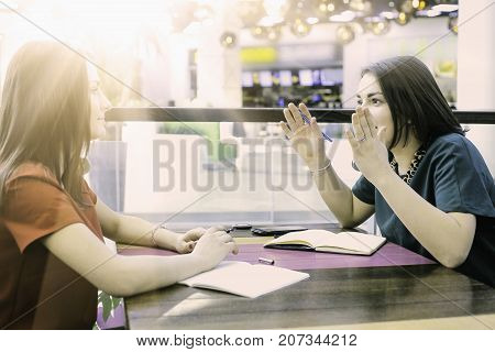 Two young female students studying together. Happy best friends with books having fun while studying. Friendship knowledge education successful and lifestyle concepts.