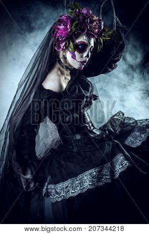 Calavera Catrina in black dress over dark background. Sugar skull makeup. Dia de los muertos. Day of The Dead. Halloween.
