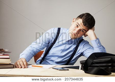 I hate my office work. Young businessman working with documents. Low wages overtime working hours lack of career prospects unfreedom concept. (Body language gestures psychology)