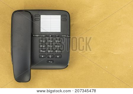 Desk phone on yellow background close up picture