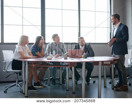 Young professional team. Group of young modern people in smart casual wear having a brainstorm meeting while sitting behind the glass wall in the creative office. Business concept.