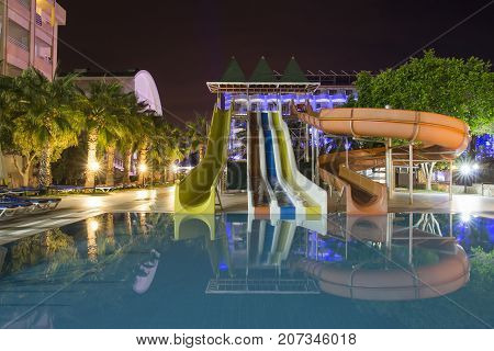 Alanya, Turkey -  August 14, 2017: territory of resort hotel with swimming pool water slides and water park at night. night landscape of Turkish tropical hotel with water park.