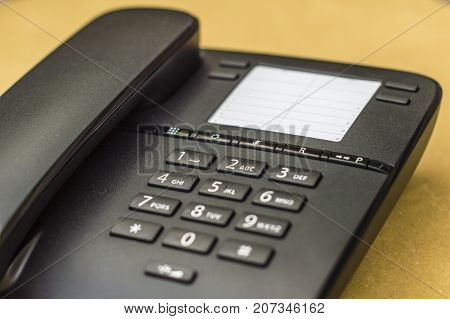 Desk phone on yellow background close up picture with blurred effect