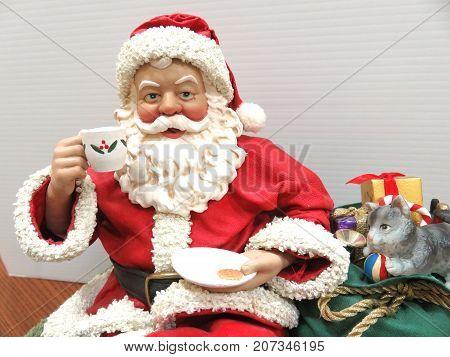 Fabric maché Santa close up head and shoulders, enjoying a cookies and tea break