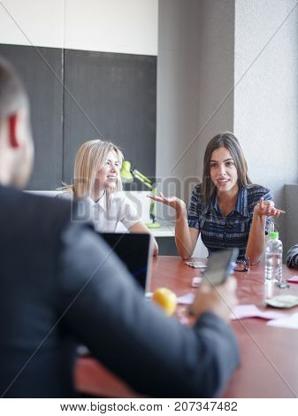 Young professional team. Pretty girl talking with boss. Group of young modern people in smart casual wear having a brainstorm meeting while sitting behind the glass wall in the creative office. Business concept.