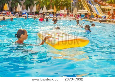 Alanya Turkey - August 14 2017: People swim in pool of resort hotel on vacation. Happy summer vacation in tropical hotel.
