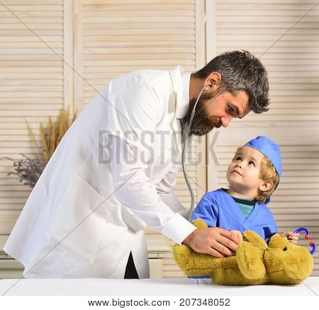 Vet And Little Assistant Examine Teddy Bear. Father And Kid